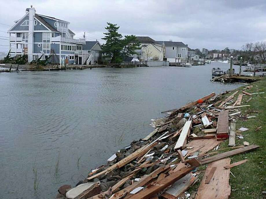 Debris from damaged homes along Fairfield Beach and Pine Creek lined the creek in October 2012 following Superstorm Sandy. A forum on the state's new Shore Up CT loan program to help owners finance the elevation of their homes is planned locally Thursday. Photo: File Photo / Fairfield Citizen