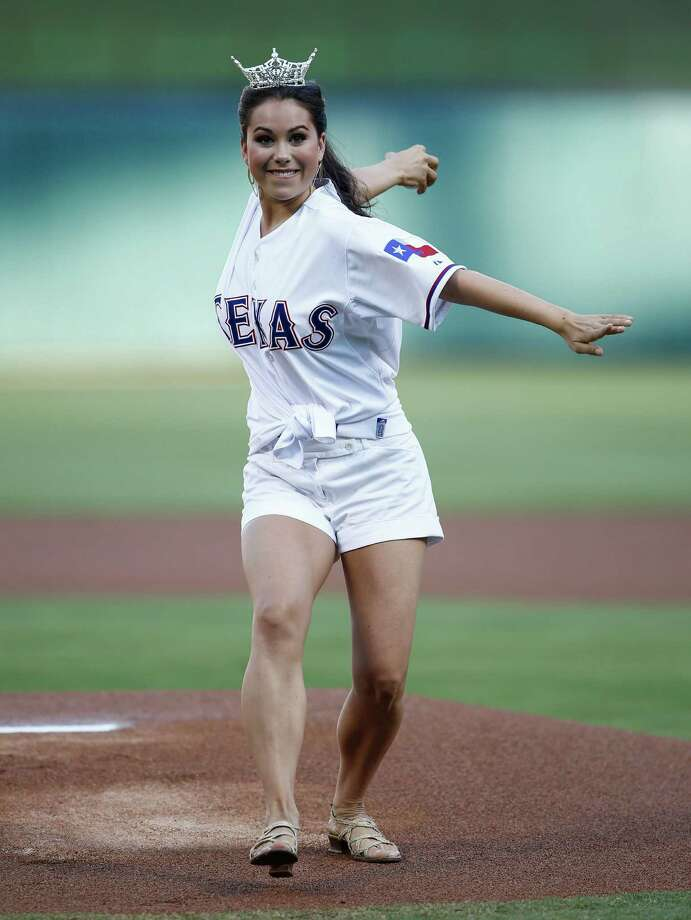 Miss Texas 2014 Monique Evans throws out the ceremonial first-pitch before the baseball between the Los Angeles Angels and the Texas Rangers, Friday, Aug. 15, 2014, in Arlington, Texas. (AP Photo/Jim Cowsert) Photo: Jim Cowsert, Associated Press / FR170531 AP