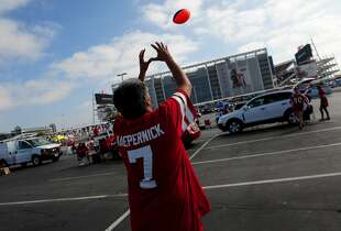 Lonnie Padilla catches a football thrown by his wife Sheri in parking lot zone green 1 outside of Levi's Stadium before the 49ers face the Denver Broncos's on August 17, 2014 in Santa Clara, CA.