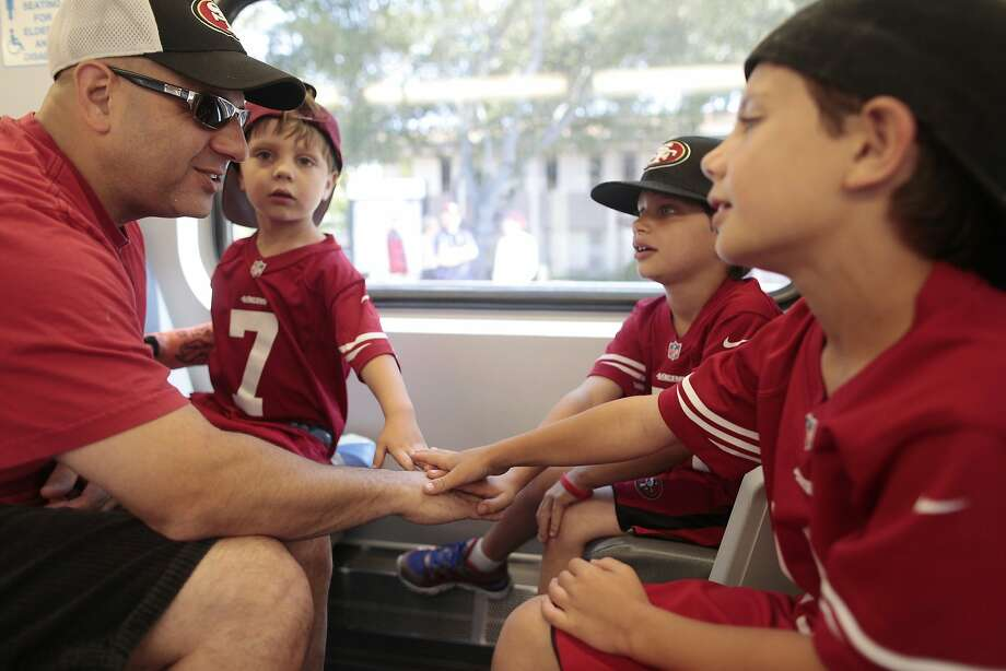 Left to right, Sateez, Colton, Caden and Baron Kadivar put their hands in while taking the Caltrain to the 49ers game on Sunday, Aug. 16, 2014 in San Francisco, Calif. 49ers fans came from all over the Bay Area to attend the first game at the Levi's Stadium. Photo: James Tensuan, The Chronicle