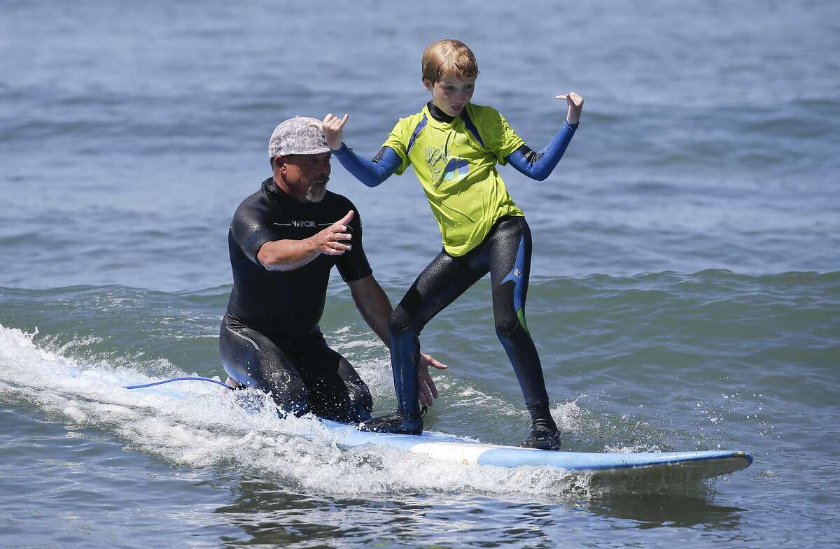 In this July 24, 2014 photo, Gavin Montelone, 8, right, gets help riding a wave from volunteer Bobby Friedman in San Clemente, Calif. Gavin and two of his siblings are part of a growing number of people with cystic fibrosis who are taking advantage of the health benefits that come with surfing. (AP Photo/Chris Carlson)