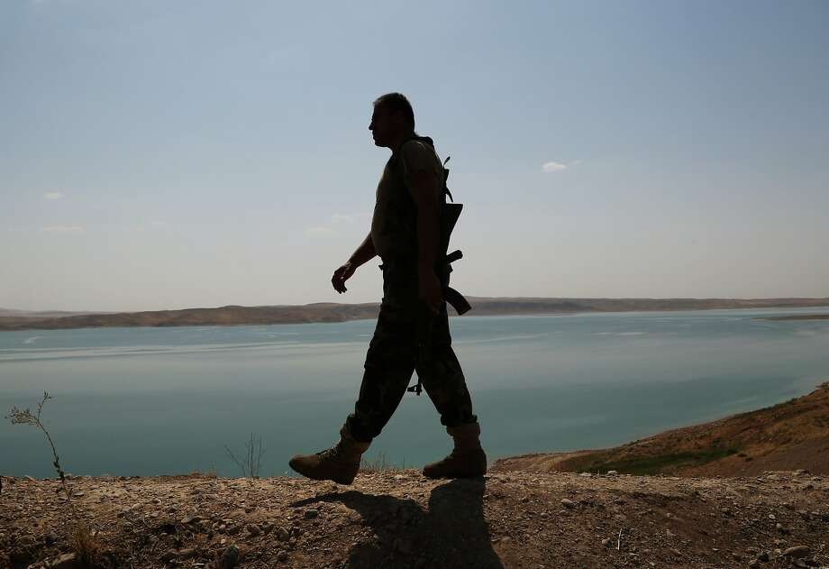 A Kurdish peshmerga fighter patrols near the Mosul Dam. Iraq's largest dam, which supplies power and water to much of the country, was captured by Islamic State fighters this month. Photo: Khalid Mohammed, Associated Press