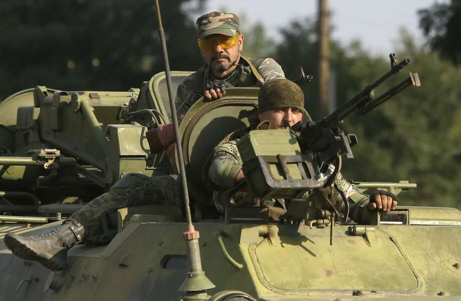 Pro-Russian rebels ride on an APC in the town of Krasnodon, eastern Ukraine, Sunday, Aug. 17, 2014. A column of several dozen heavy vehicles, including tanks and at least one rocket launcher, rolled through rebel-held territory on Sunday.(AP Photo/Sergei Grits) Photo: Sergei Grits, Associated Press