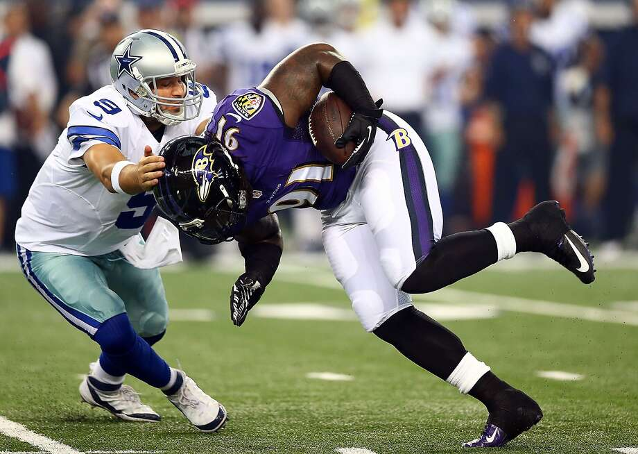 Dallas quarterback Tony Romo tries to tackle Ravens linebacker Courtney Upshaw in Baltimore's 37-30 preseason win Saturday. Romo completed 4 of 5 passes for 80 yards. Photo: Ronald Martinez, Getty Images