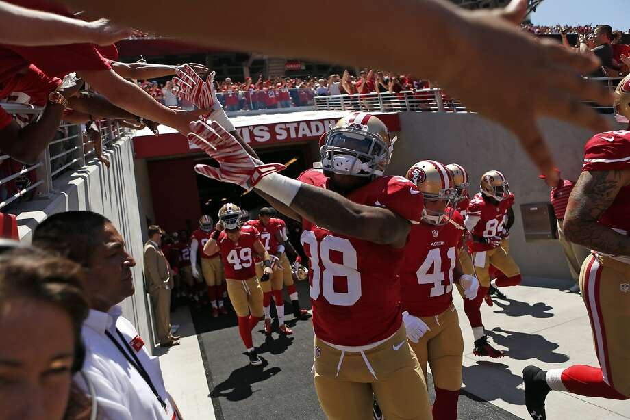 Rookie cornerback Kenneth Acker greets fans as the 49ers take the field for the first time at Levi's Stadium. The lopsided score - Denver won 34-0 - led many fans to leave their seats and explore the new stadium. Photo: Scott Strazzante, The Chronicle