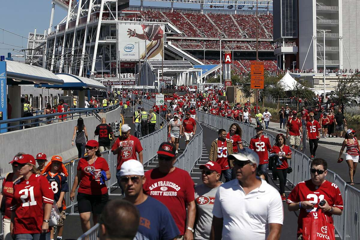 49er's fans walk along fencing leading them to a VTA light rail station as they leave Levi's Stadium during halftime of the first preseason football game between the San Francisco 49ers and the Denver Broncos in Santa Clara, CA, Sunday, August 17, 2014.