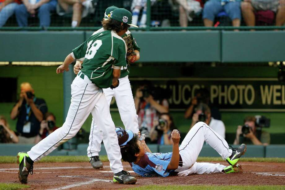 Philadelphia's Jack Rice (2) is tagged out attempting to score by Pearland pitcher Clayton Broeder, center, during the first inning of a baseball game at the Little League World Series tournament in South Williamsport, Pa., Sunday, Aug. 17, 2014. Rice, who was tagged in the face, was injured on the play. (AP Photo/Gene J. Puskar Photo: Gene J. Puskar, Associated Press / AP