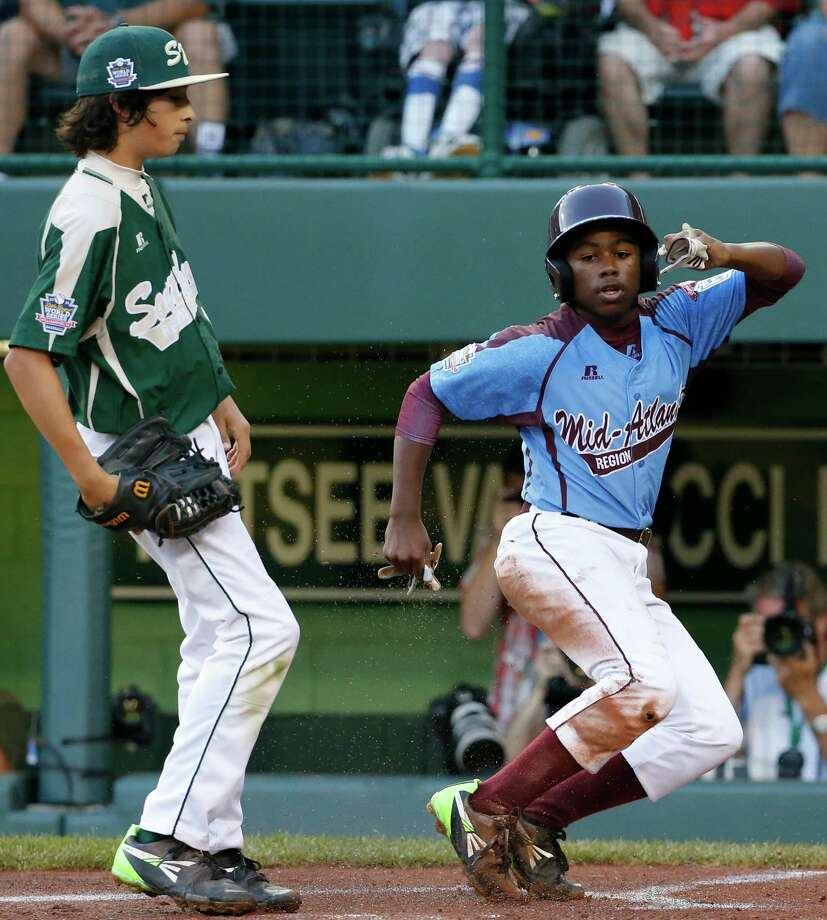 Philadelphia's Jahli Hendricks, right, scores on a wild pitch by Pearland  pitcher Clayton Broeder, left, during the first inning of a baseball game at the Little League World Series tournament in South Williamsport, Pa., Sunday, Aug. 17, 2014. (AP Photo/Gene J. Puskar Photo: Gene J. Puskar, Associated Press / AP