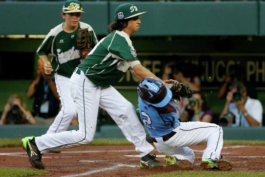Philadelphia's Jack Rice (2) is tagged out attempting to score by Pearland pitcher Clayton Broeder, center, during the first inning of a baseball game at the Little League World Series tournament in South Williamsport, Pa., Sunday, Aug. 17, 2014. Rice, who was tagged in the face, was injured on the play. (AP Photo/Gene J. Puskar) Photo: Gene J. Puskar, Associated Press / AP