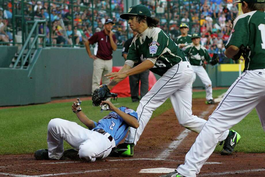 Philadelphia's Jack Rice, left, is tagged out attempting to score by  Pearland pitcher Clayton Broeder (18) during the first inning of a baseball game in United States pool play at the Little League World Series tournament in South Williamsport, Pa., Sunday, Aug. 17, 2014. Rice, who was tagged in the face, was injured on the play. (AP Photo/Gene J. Puskar) Photo: Gene J. Puskar, Associated Press / AP