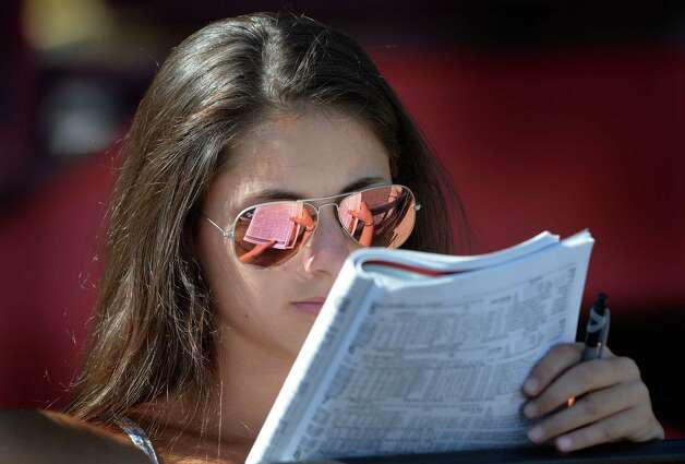 Emma Saros, 15, of Centerport N.Y. tries her hand at handicapping the card at the Saratoga Race Course Sunday afternoon Aug. 17, 2014.  She didn't pick a winner but her little sister picked four winners in a row.  Perhaps beginners luck.   (Skip Dickstein/Times Union) Photo: SKIP DICKSTEIN