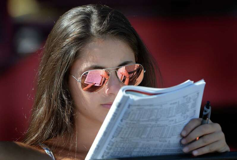 Emma Saros, 15, of Centerport N.Y. tries her hand at handicapping the card at the Saratoga Race C