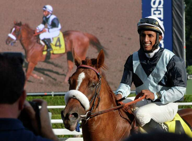 Jockey Rajiv Maragh smiles as he returns to the winners circle with Main Sequence after winning the