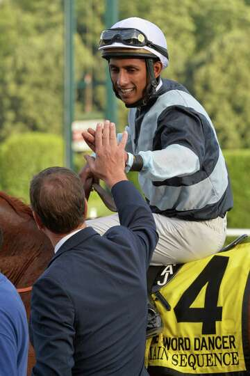 Jockey Rajiv Maragh gets a high five from trainer Graham Motion as he returns to the winners circle