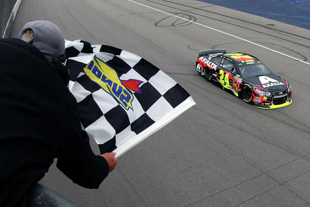 Jeff Gordon takes the checkered flag to win the NASCAR Sprint Cup Series Pure Michigan 400 auto race at Michigan International Speedway on Sunday, Aug. 17, 2014, in Brooklyn, Mich.  (AP Photo/Brian Lawdermilk, Pool) ORG XMIT: MIPS117 Photo: Brian Lawdermilk / Getty Pool