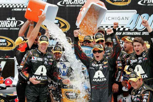 Jeff Gordon celebrates his victory with crew members after the NASCAR Sprint Cup Series Pure Michigan 400 auto race at Michigan International Speedway in Brooklyn, Mich., Sunday, Aug. 17, 2014. (AP Photo/Bob Brodbeck) ORG XMIT: MIPS114 Photo: Bob Brodbeck / FR3471 AP