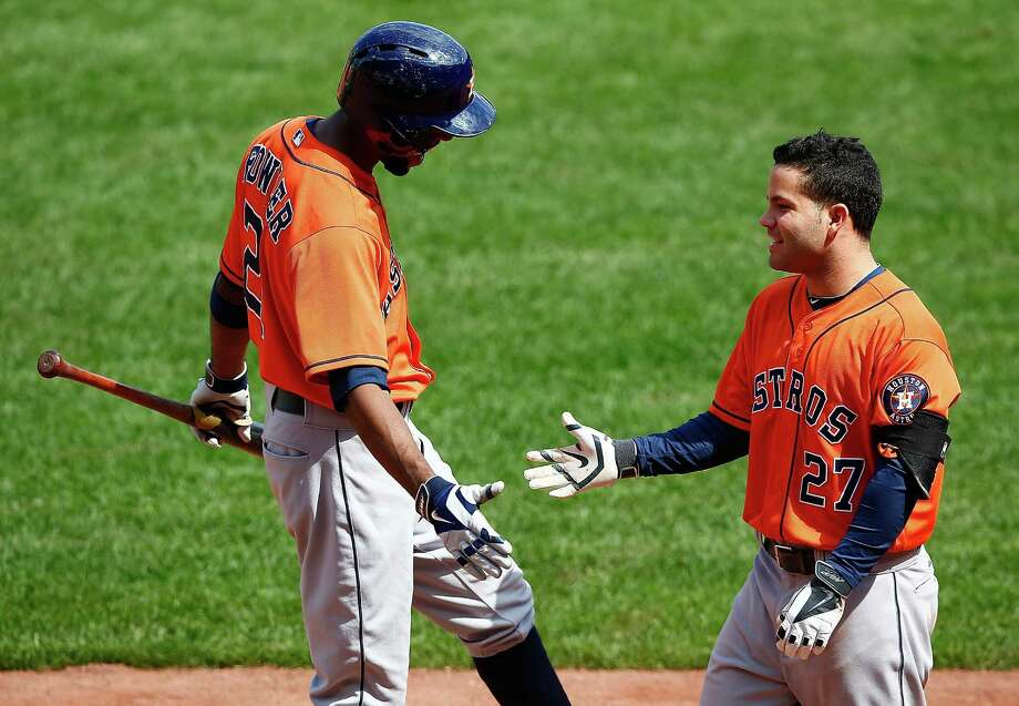 Life was grand for Jose Altuve, right, on Sunday as his second-inning slam earned congratulations from Dexter Fowler and came after an overturned double play gave new life to the inning. Photo: Jared Wickerham, Stringer / 2014 Getty Images