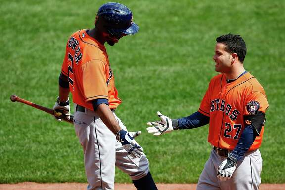 Life was grand for Jose Altuve, right, on Sunday as his second-inning slam earned congratulations from Dexter Fowler and came after an overturned double play gave new life to the inning.