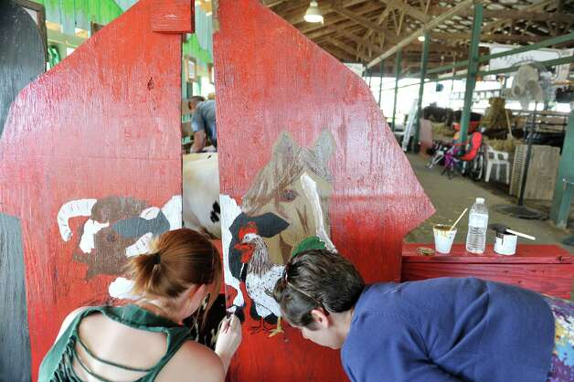Sister-in-laws, Kate Monroe, left, from Fort Ann and Marcia Monroe from Ballston Lake paint a picture of farm animals for the Monroe Family Farm display as set up continues for the Washington County Fair on Sunday, August 17, 2014, in Greenwich, N.Y.  Other members of the family will be showing beef cows at the fair on Thursday and Friday.  The fair opens at 5 p.m. on Monday.  (Paul Buckowski / Times Union) Photo: Paul Buckowski / 00028207A