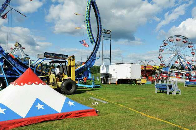Workers set up the rides and games as they prepare for the opening of the Washington County Fair on Sunday, August 17, 2014, in Greenwich, N.Y.  The fair opens at 5 p.m. on Monday.  (Paul Buckowski / Times Union) Photo: Paul Buckowski / 00028207A