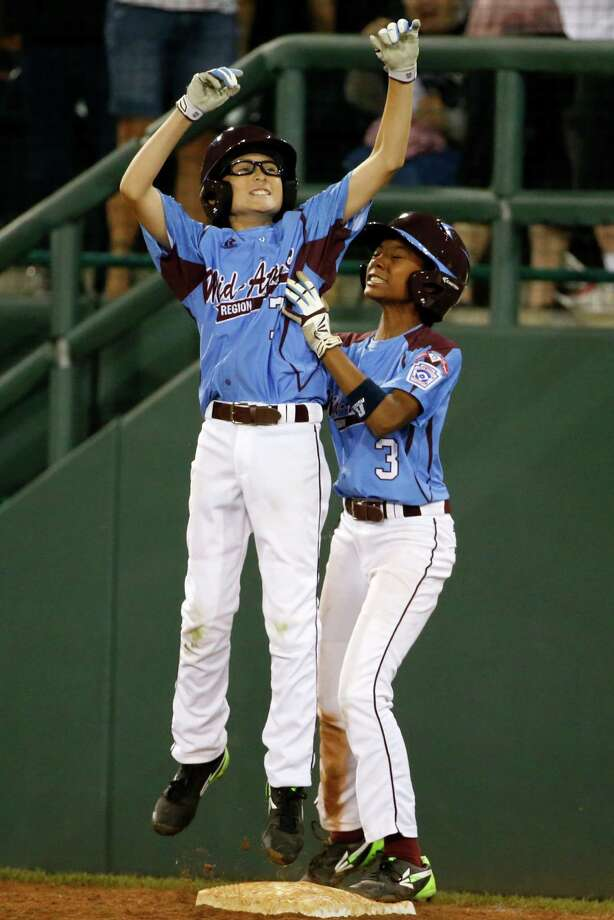 Philadelphia's Tai Shanahan (7) celebrates his walk-off single with teammate Mo'ne Davis (3) during the sixth inning of a baseball game against Pearland in United States pool play at the Little League World Series tournament in South Williamsport, Pa., Sunday, Aug. 17, 2014. Philadelphia won 7-6. (AP Photo/Gene J. Puskar Photo: Gene J. Puskar, Associated Press / AP