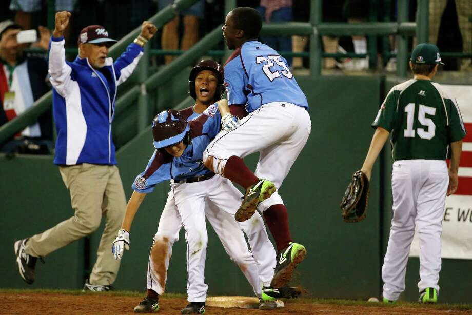 Philadelphia's Tai Shanahan, left center,  celebrates his walk-off single with teammate Mo'ne Davis, center rear, and Zion Spearman (25) during the sixth inning of a baseball game against Pearland in United States pool play at the Little League World Series tournament in South Williamsport, Pa., Sunday, Aug. 17, 2014. Philadelphia won 7-6. (AP Photo/Gene J. Puskar Photo: Gene J. Puskar, Associated Press / AP