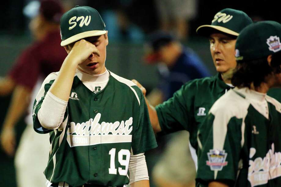 Pearland's Jonathan Newman (19) is consoled by manager Don Smith, right rear, as they walk off the field after a 7-6 loss to Philadelphia in a baseball game in United States pool play at the Little League World Series tournament in South Williamsport, Pa., Sunday, Aug. 17, 2014. (AP Photo/Gene J. Puskar) Photo: Gene J. Puskar, Associated Press / AP