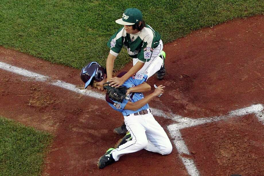 Philadelphia's Jack Rice, bottom, is tagged out attempting to score by  Pearland pitcher Clayton Broeder (18) during the first inning of a baseball game in United States pool play at the Little League World Series tournament in South Williamsport, Pa., Sunday, Aug. 17, 2014. Rice was injured on the play and did not remain in the game. Philadelphia won 7-6. (AP Photo/Gene J. Puskar Photo: Gene J. Puskar, Associated Press / AP