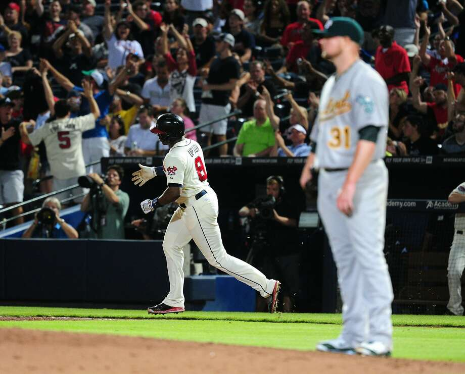 Justin Upton rounds the bases after homering off the A's Jon Lester. Photo: Scott Cunningham, Getty Images