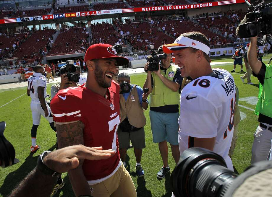 Colin Kaepernick and Peyton Manning chat after their very different performances. Photo: Carlos Avila Gonzalez, The Chronicle