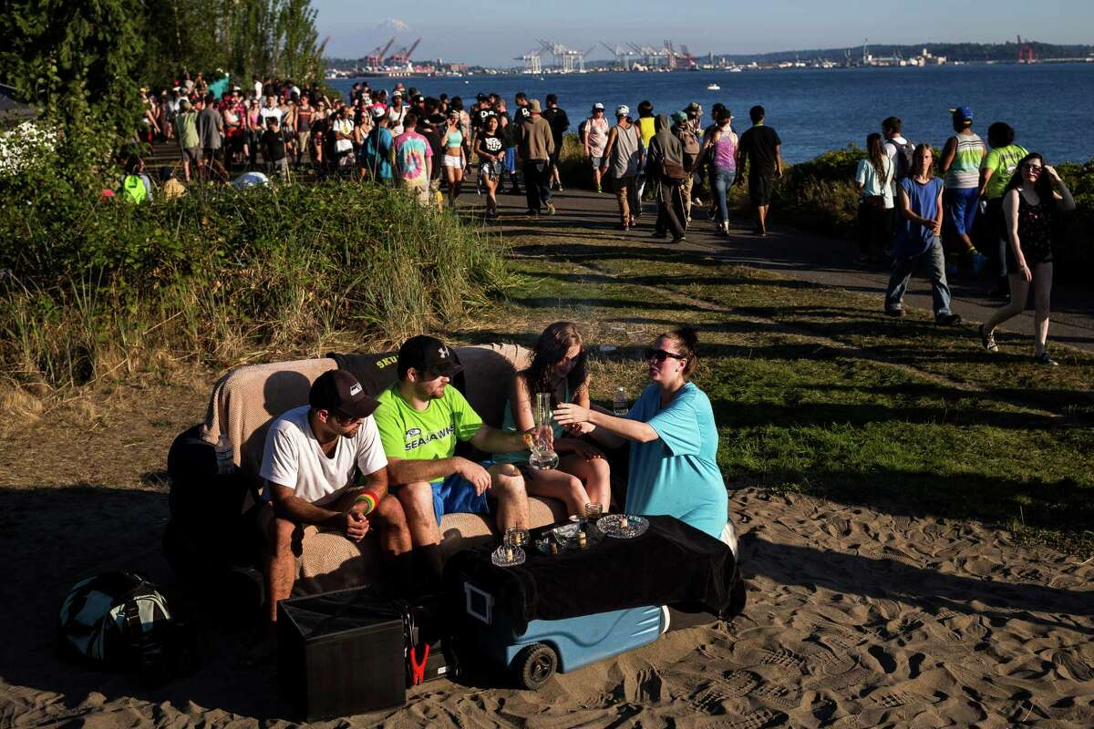 From left, Tommy Tompson and Jake Rossi, owners of Jettrays, share their bong with Darci Board and Desiree Dell from their seat on a portable, inflatable couch with a view of Mount Rainier in the background on the final day of Hempfest, Seattle's annual gathering to advocate the decriminalization of marijuana, photographed Sunday, August 17, 2014, at Myrtle Edwards Park on the Seattle waterfront in Seattle, Washington. The three-day annual event includes political rallies, concerts, and an arts and crafts fair.