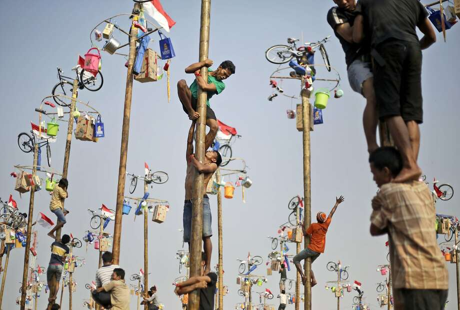 Participants struggle to reach the prizes during a greased-pole climbing competition held as a part of the Independence Day celebrations in Jakarta, Indonesia, Sunday, Aug. 17, 2014. Indonesia is celebrating its 69th independence from the Dutch colonial rule. (AP Photo/Dita Alangkara) Photo: Dita Alangkara, Associated Press
