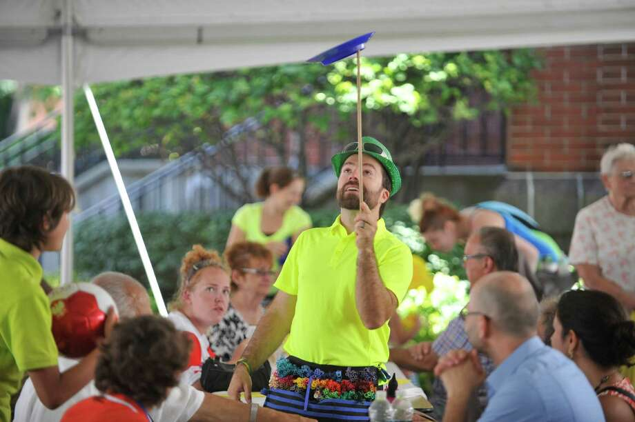 Scott Murawski, from Amsterdam, playing the part of Scotty Nut Nut, spins a plate as he entertains guests at the Schenectady Polish American Festival at Saint Adalberts Church on Sunday, Aug. 17, 2014, in Schenectady, N.Y.  This is the 29th year of the festival for the church which is over 100 years old.  Volunteers cooked up 4,200 pierogis and 1,200 kielbasa and 1,200 golabki for the two-day event.  The festival is the largest fund raising event for the church which has 650 families as members.   (Paul Buckowski / Times Union) Photo: Paul Buckowski / 00028202A