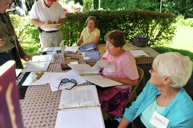 Carole McCarthy, background, from Duxbury, MA, Phyllis Budka Zych, center, from Niskayuna and Bernice Izzo, right, from Niskayuna, help people with their Polish genealogy at the Schenectady Polish American Festival at Saint Adalberts Church on Sunday, Aug. 17, 2014, in Schenectady, N.Y.  The women are working on compiling a database to discover Schenectady County's Eastern European roots.  This is the 29th year of the festival for the church which is over 100 years old.  Volunteers cooked up 4,200 pierogis and 1,200 kielbasa and 1,200 golabki for the two-day event.  The festival is the largest fund raising event for the church which has 650 families as members.   (Paul Buckowski / Times Union) Photo: Paul Buckowski / 00028202A