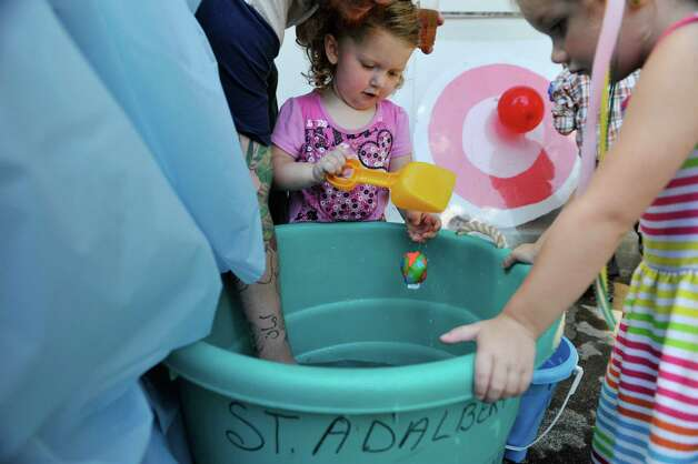 Ivy McCullough, 2, from Amsterdam plays in a bucket of water in the kid's game area at the Schenectady Polish American Festival at Saint Adalberts Church on Sunday, Aug. 17, 2014, in Schenectady, N.Y.  This is the 29th year of the festival for the church which is over 100 years old.  Volunteers cooked up 4,200 pierogis and 1,200 kielbasa and 1,200 golabki for the two-day event.  The festival is the largest fund raising event for the church which has 650 families as members.   (Paul Buckowski / Times Union) Photo: Paul Buckowski / 00028202A