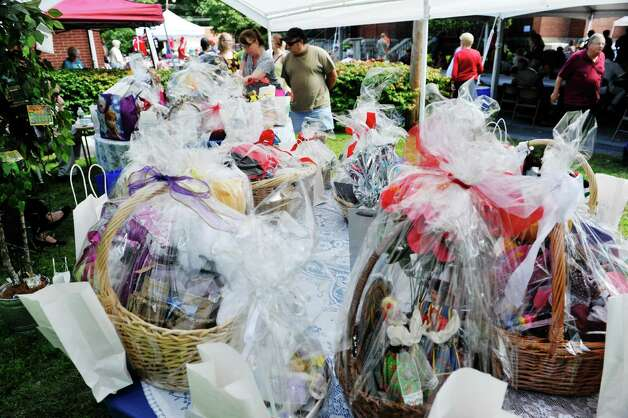 People look over the items that are part of the basket raffle  at the Schenectady Polish American Festival at Saint Adalberts Church on Sunday, Aug. 17, 2014, in Schenectady, N.Y.  This is the 29th year of the festival for the church which is over 100 years old.  Volunteers cooked up 4,200 pierogis and 1,200 kielbasa and 1,200 golabki for the two-day event.  The festival is the largest fund raising event for the church which has 650 families as members.   (Paul Buckowski / Times Union) Photo: Paul Buckowski / 00028202A
