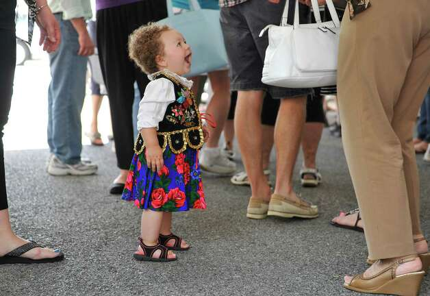 Maya Harding, 14 months old, wearing a traditional dress from southern Poland, greets people at the Schenectady Polish American Festival at Saint Adalberts Church on Sunday, Aug. 17, 2014, in Schenectady, N.Y.  This is the 29th year of the festival for the church which is over 100 years old.  Volunteers cooked up 4,200 pierogis and 1,200 kielbasa and 1,200 golabki for the two-day event.  The festival is the largest fund raising event for the church which has 650 families as members.   (Paul Buckowski / Times Union) Photo: Paul Buckowski / 00028202A