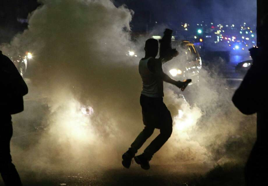 Protesters run when the police shoot tear gas in Ferguson, Mo., Sunday, Aug. 17, 2014. Protests over the killing of 18-year-old Michael Brown by a white police officer have entered their second week. Photo: J.B. Forbes, AP / St. Louis Post-Dispatch