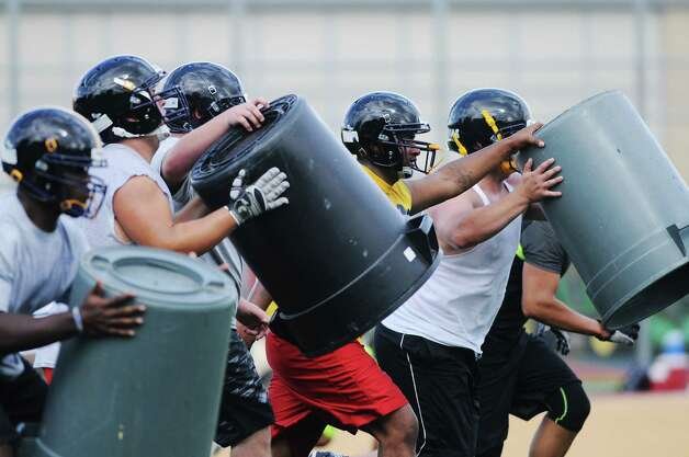Linemen use garbage cans in a drill during Troy High School football practice on Monday, Aug. 18, 2014, at Troy High School in Troy, N.Y. (Paul Buckowski / Times Union) Photo: Paul Buckowski / 00028217A