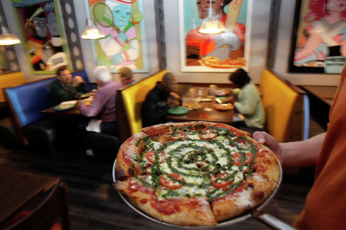 Jesse Cole, general manager, carries a Kosmic Karma pizza at Mellow Mushroom.