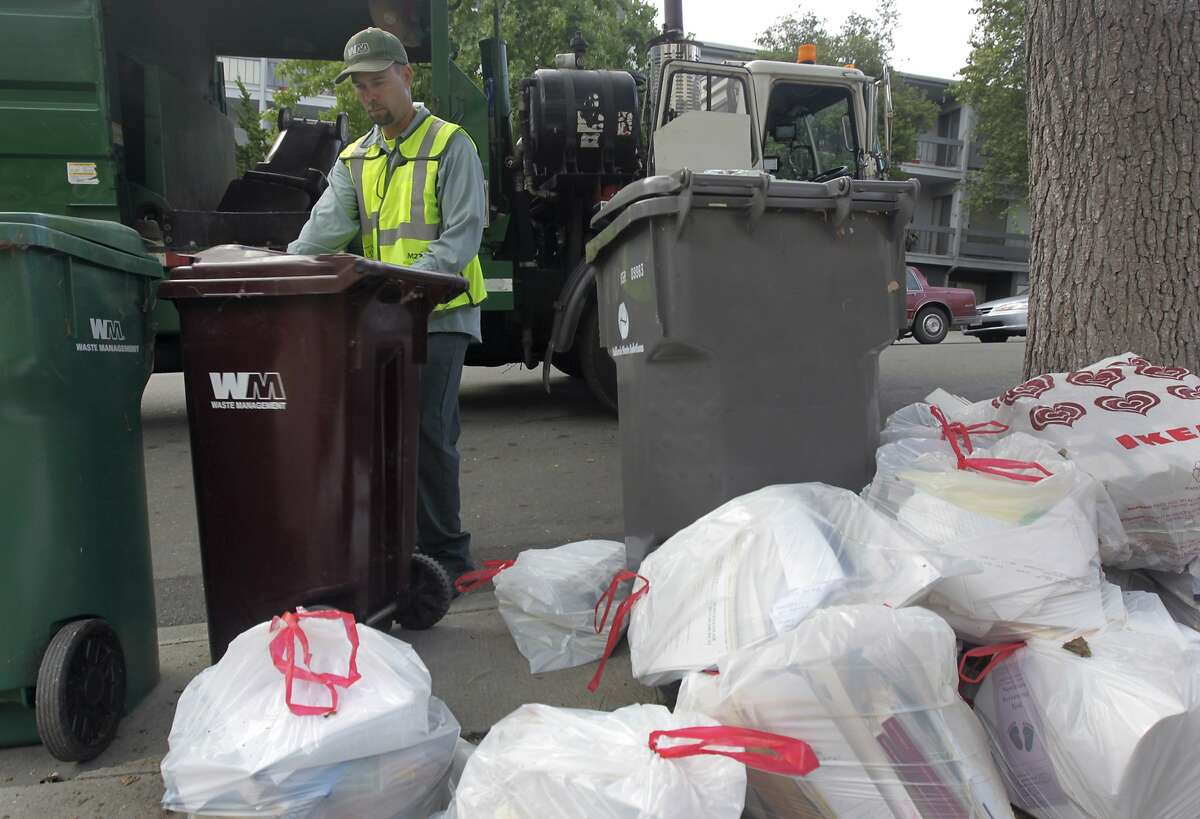 Steve Cunningham empties residential trash bins for Waste Management in the Adams Point neighborhood of Oakland, Calif. on Tuesday, Aug. 12, 2014. The city of Oakland is negotiating a new refuse collection deal with Waste Management, which currently holds the contract, and a competing firm.