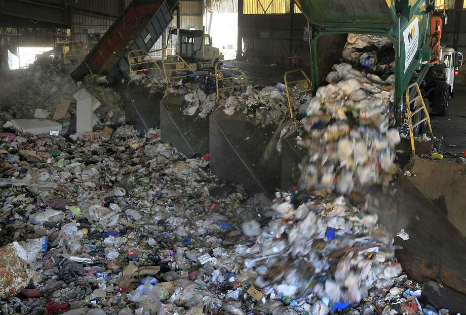 Residential trash cascades from a collection truck at the Waste Management transfer facility in San Leandro, Calif. on Tuesday, Aug. 12, 2014. The facility processes 3,400 tons of refuse daily. The city of Oakland is negotiating a new refuse collection deal with Waste Management, which currently holds the contract, and a competing firm. Photo: Paul Chinn, The Chronicle