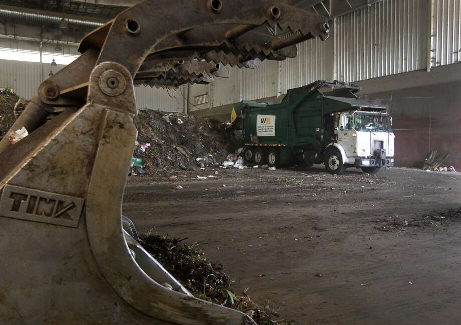 A truck unloads compostable waste collected from commercial locations at the Waste Management transfer facility in San Leandro, Calif. on Tuesday, Aug. 12, 2014. The facility processes 3,400 tons of refuse daily. The city of Oakland is negotiating a new refuse collection deal with Waste Management, which currently holds the contract, and a competing firm. Photo: Paul Chinn, The Chronicle