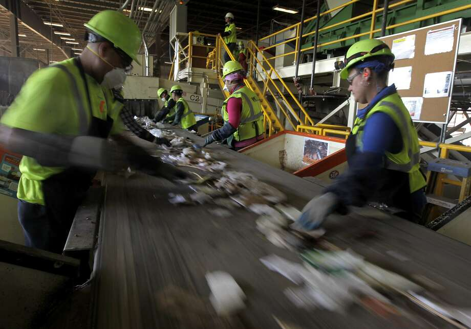 Employees separate recyclable items from commercial trash at the Waste Management transfer facility in San Leandro, Calif. on Tuesday, Aug. 12, 2014. The facility processes 3,400 tons of refuse daily. The city of Oakland is negotiating a new refuse collection deal with Waste Management, which currently holds the contract, and a competing firm. Photo: Paul Chinn, The Chronicle