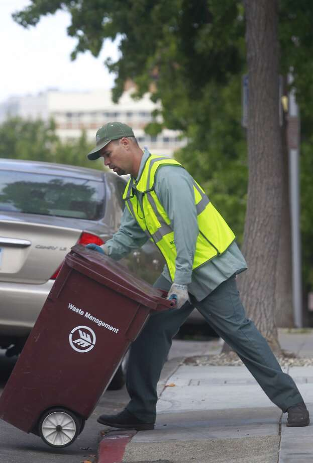 Steve Cunningham empties residential trash bins for Waste Management in the Adams Point neighborhood of Oakland, Calif. on Tuesday, Aug. 12, 2014. The city of Oakland is negotiating a new refuse collection deal with Waste Management, which currently holds the contract, and a competing firm. Photo: Paul Chinn, The Chronicle