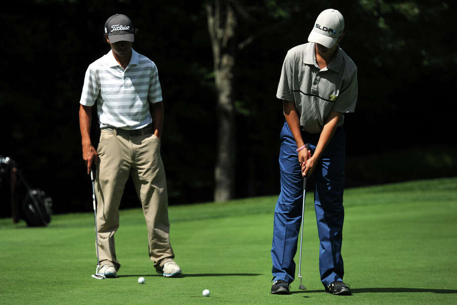 Kyle Poeti, of New Milford, sinks a putt during the Fran McCarthy Junior Golf Tournament at the Richter Park Golf Course, in Danbury, Conn. Aug. 18, 2014. Poeti is seen here with Alec Knupp of Ridgefield. Photo: Ned Gerard / Connecticut Post