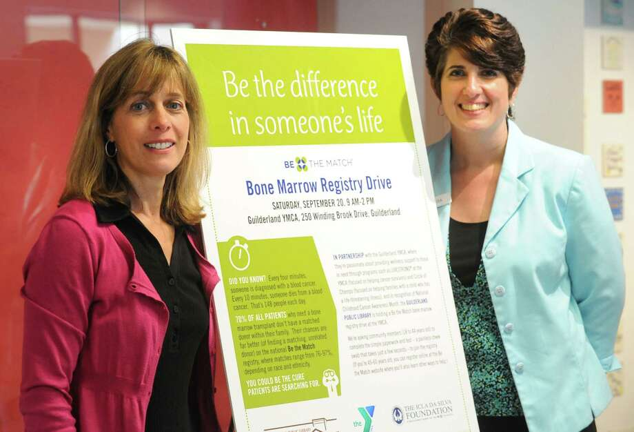 Maria Buhl, left, and Lisa Wolcott stand in front of a poster promoting their bone marrow registry event at the Guilderland YMCA on Friday, Aug. 15, 2014, in Guilderland, N.Y.  (Michael P. Farrell/Times Union) Photo: Michael P. Farrell / 00028174A