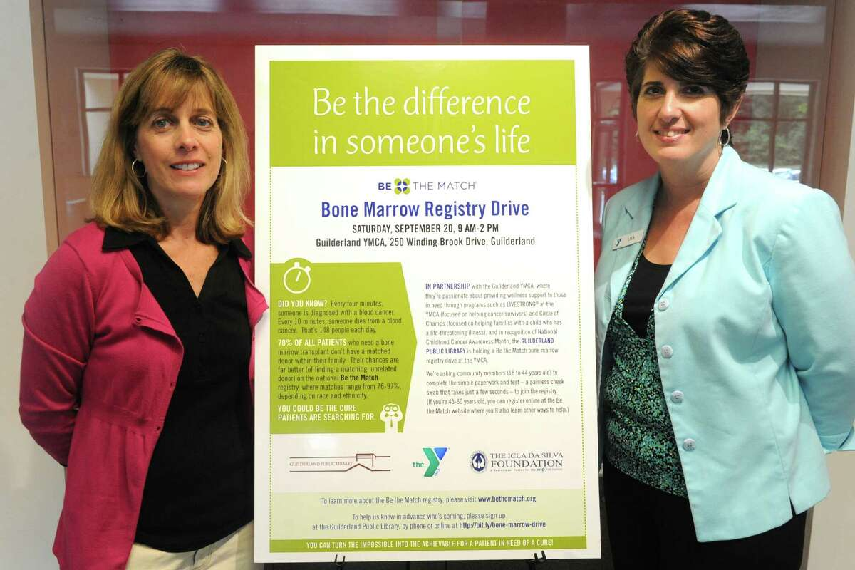 Maria Buhl, left, and Lisa Wolcott stand in front of a poster promoting their bone marrow registry event at the Guilderland YMCA on Friday, Aug. 15, 2014, in Guilderland, N.Y. (Michael P. Farrell/Times Union)