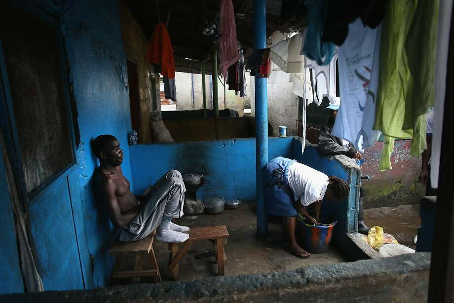 A man who said he was showing symptoms of Ebola in New Kru Town, Liberia, listens to health workers. The virus has killed more than 1,000 people in four West African countries, and Liberia has the most. Photo: John Moore, Getty Images