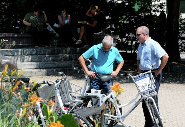 Wendall Thayer of Voorheesville, left, and Louis Klender of Latham, right, look over some of Albany's BikeShare week bicycles available to share Monday, Aug. 11, 2014, at Tricentennial Square in Albany, N.Y. (Will Waldron/Times Union) Photo: WW / 00028107A